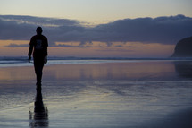 man walking in wet sand on a shore at dusk