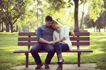 Man comforting his wife on a park bench.