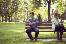 a fighting couple sitting on a park bench looking away from one another