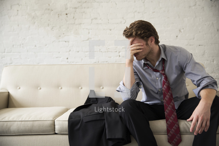 a stressed and frustrated businessman sitting on a couch