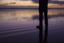 man's legs standing on wet sand on a beach