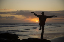 man with crane pose on a beach at sunset
