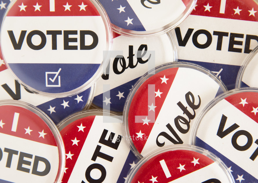 """Patriotic colored buttons reading, """"Vote,"""" and """"I Voted."""""""