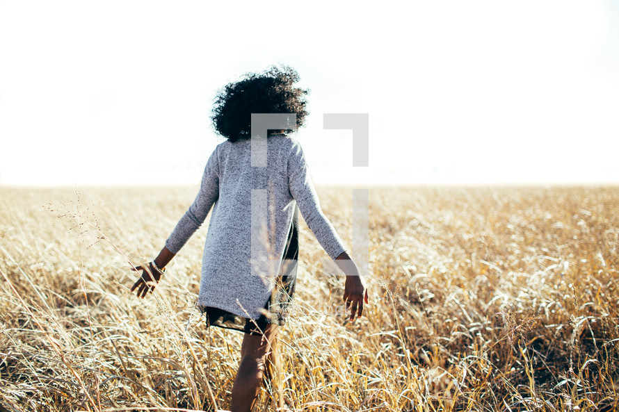 a woman walking through a field