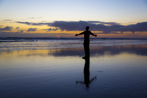 silhouette of a man with open arms standing on a beach