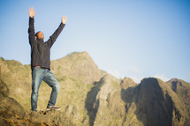 African American man standing on rock cliff with raised hands