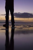 legs standing on wet sand
