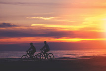 Two male cyclists bike down the beach at sunset.