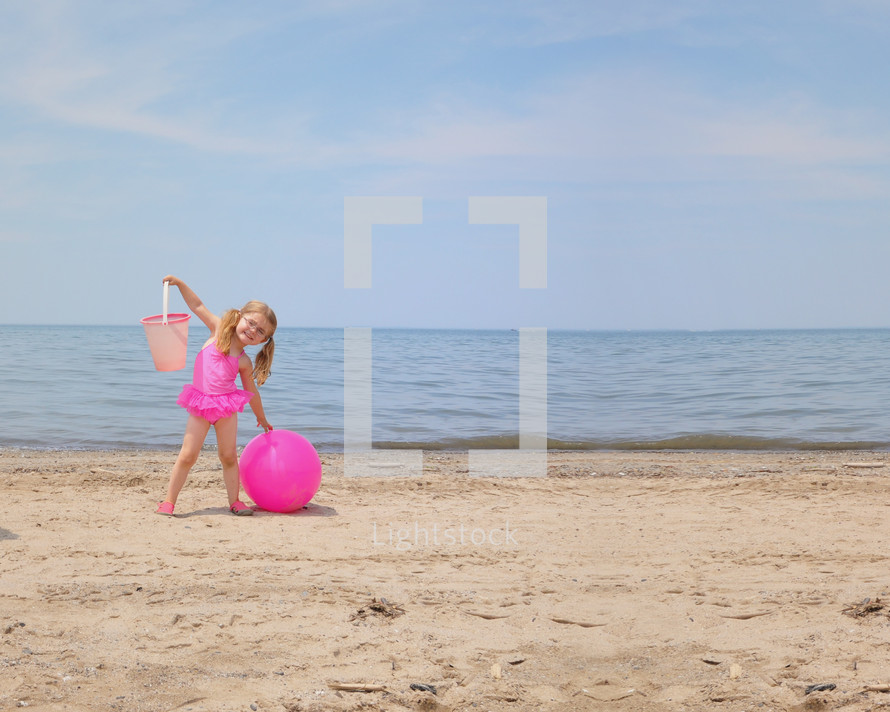 a little girl on a beach with a sand bucket and ball