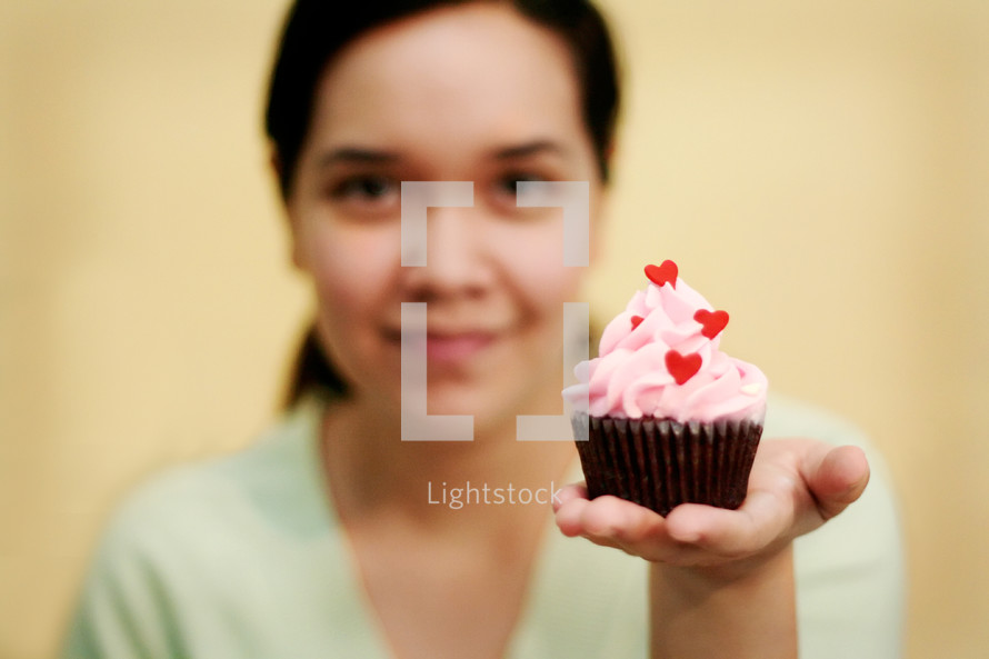 A woman holding a Valentine's cupcake