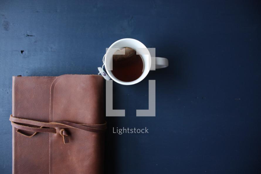 coffee mug and leather bound Bible