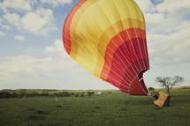 Hot air ballon taking off in a field