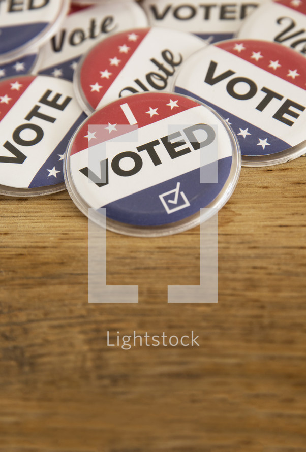 """Political buttons reading, """"Vote,"""" and """"I Voted"""" on wood table."""