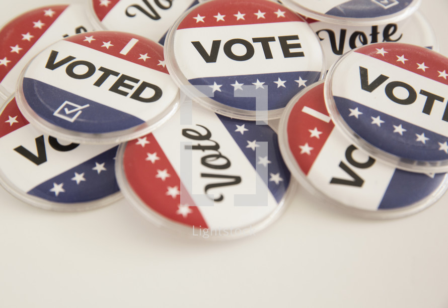 """Patriotic buttons reading, """"Vote,"""" and """"I Voted."""""""