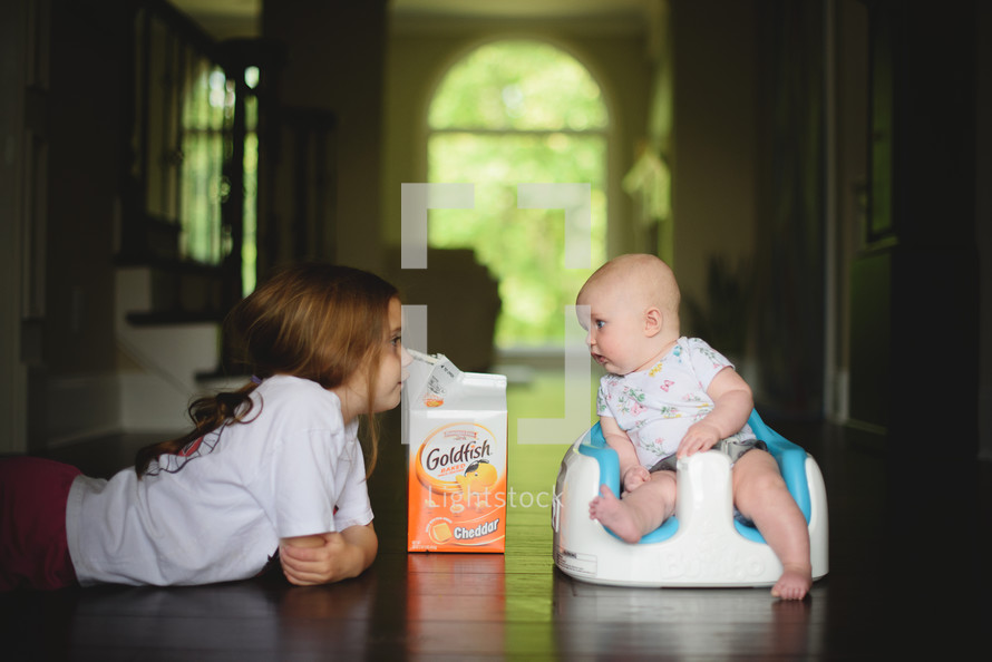 siblings on a wood floor with goldfish