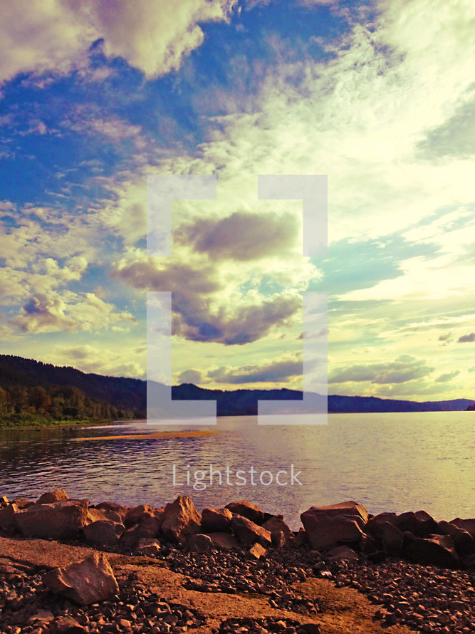 Clouds over the silhouette of a mountain range by the ocean shore.