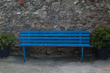 An empty blue bench against a rock wall.