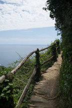 A path with a rustic railing near a lake.
