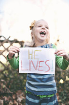 """girl holding a sign that says """"He lives"""""""