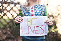 """girl child holding a sign that says """"He Lives!"""""""