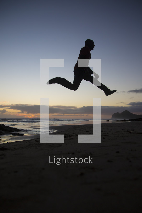 silhouette of a man leaping on a beach