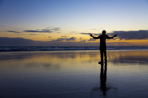silhouette of a man standing on wet sand with hands raised in worship
