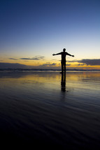man with open arms at a beach at sunset
