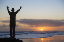 silhouette of a man standing on a beach with hands raised in worship