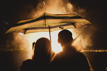 A couple standing under an umbrella watching fireworks