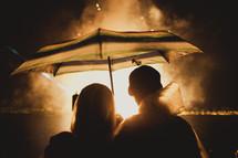 A couple standing under an umbrella watching fireworks