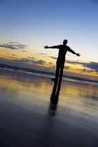 man with open arms standing on a beach
