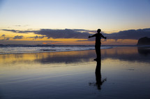 silhouette of a man standing on a beach at sunset with open arms