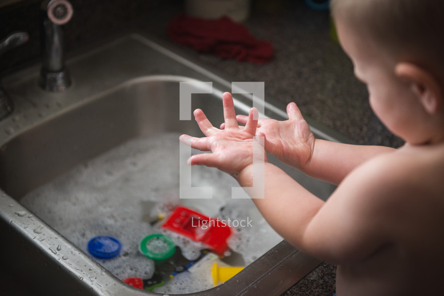 an infant playing in a sink