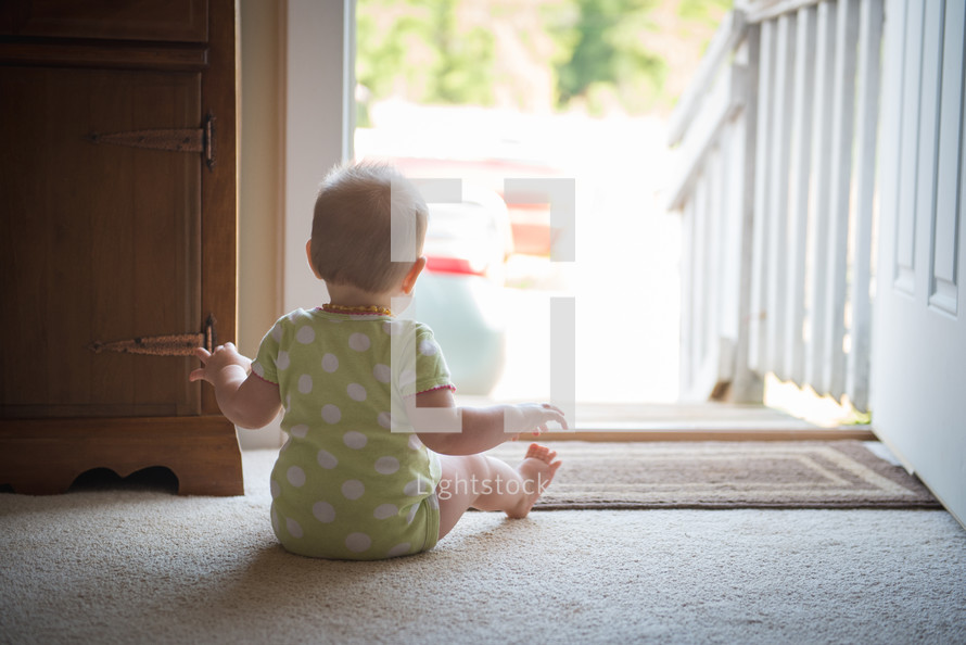 an infant sitting in front a door