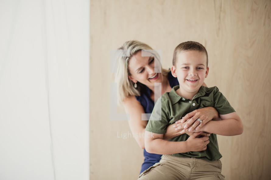 happy mother and son sitting on a stool