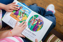 sisters reading a children's Bible together
