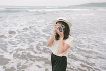 a woman holding a camera standing on a beach