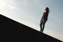 woman walking on the edge of a concrete wall