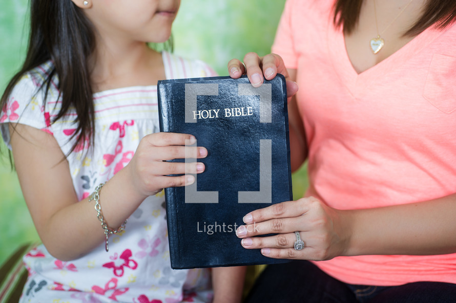 Mother handing Bible to her daughter.