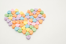 Candy hearts forming a heart shape.