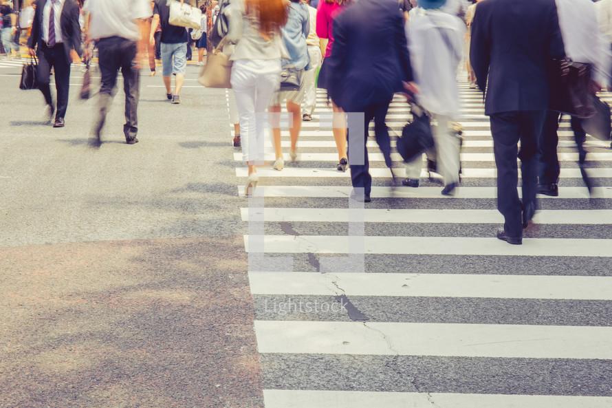 people crossing a busy crosswalk