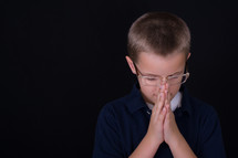 A boy child with glasses praying
