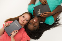 Teen girls holding Bibles against their hearts.