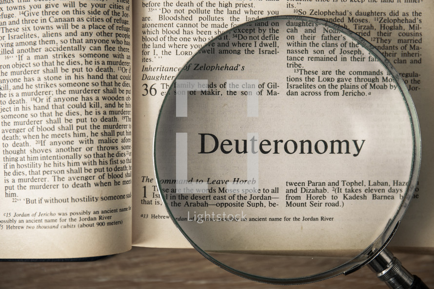 magnifying glass over Bible - Deuteronomy
