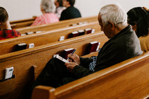 church visitor filling out an information card in a church pew