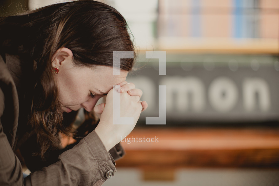 woman with head bowed in prayer