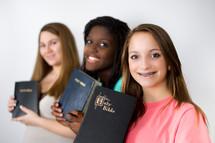 smiling teen girls holding Bibles