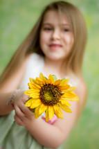 little girl holding a sunflower