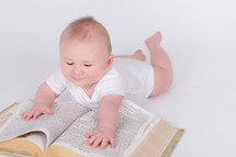 Infant laying on the floor, hands stretched out on a giant bible