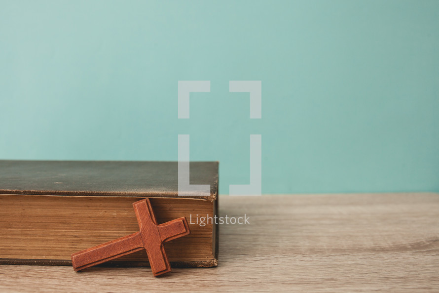 wood cross and spine of a Bible
